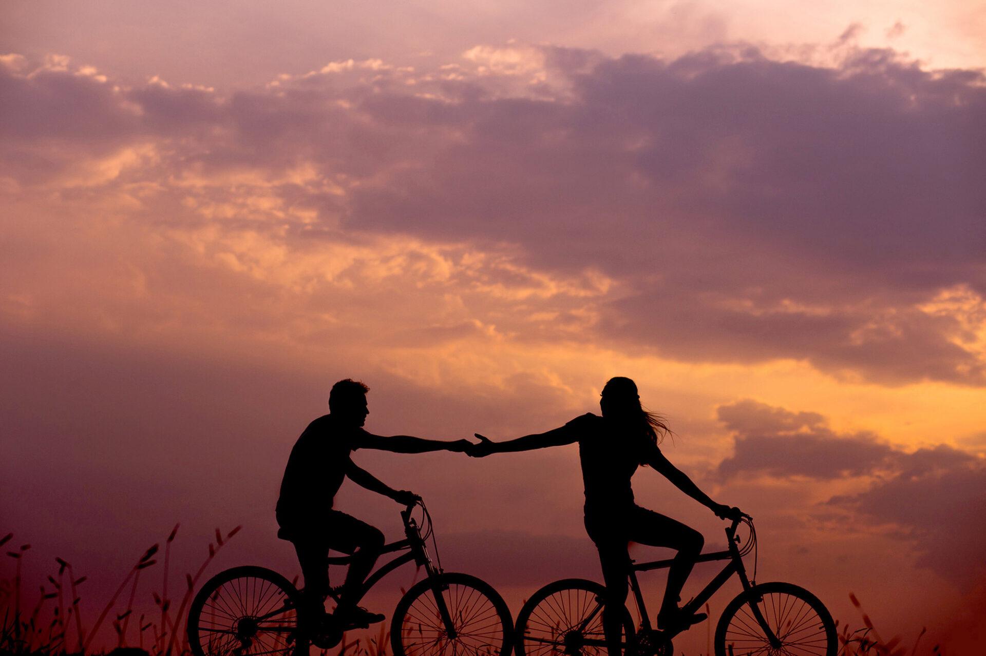 ερωτευμένο ζευγάρι που κάνει ποδήλατο στο ηλιοβασίλεμα